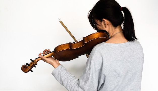 Parte posterior de la mujer tocando el violín, presionando la cuerda con la mano