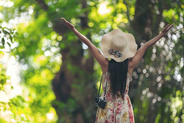 La parte posterior de la niña de la felicidad con un sombrero de paja en el jardín