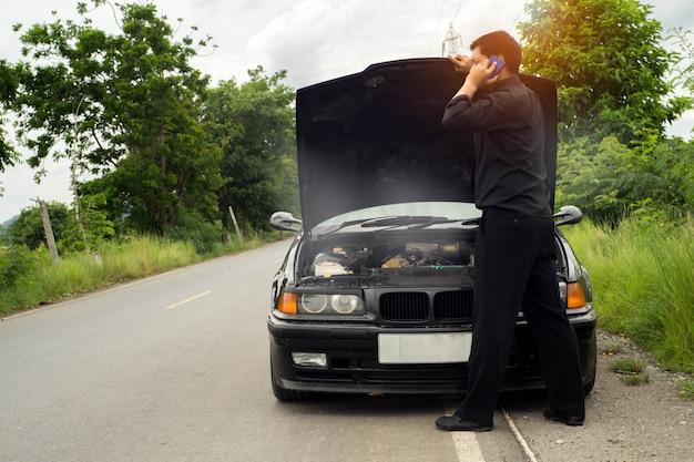 La parte posterior del técnico sostiene el destornillador para la reparación del automóvil, un automóvil roto con humo