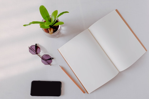Parte superior de la apertura del cuaderno en blanco con lápiz, teléfono inteligente, mesa blanca gafas de sol