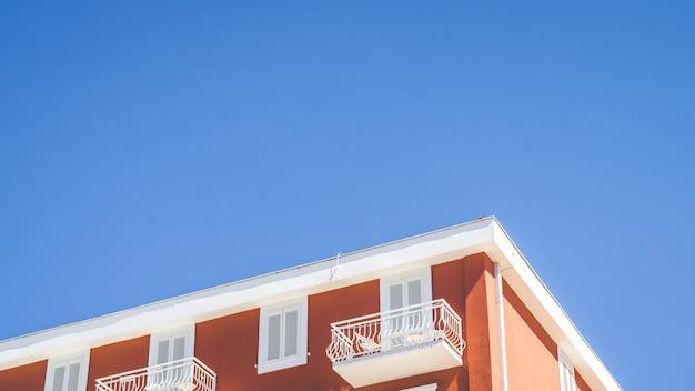 Parte superior de un edificio naranja con un balcón blanco y una ventana con un cielo azul claro en el fondo