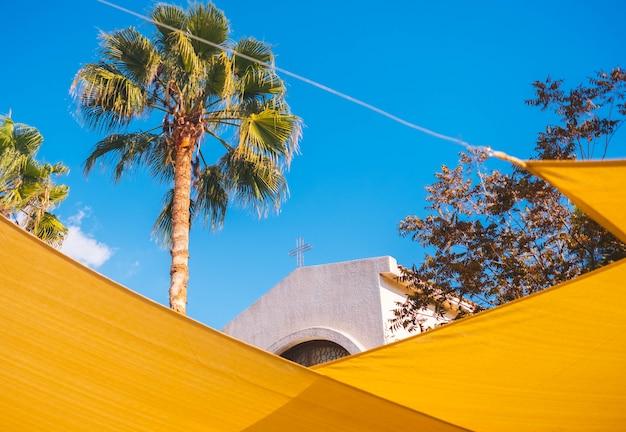 La parte superior de la iglesia a través de decoraciones amarillas de la calle.