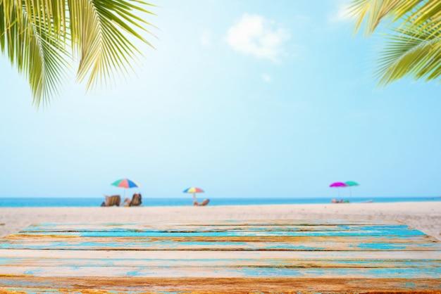 Parte superior de la mesa de madera con paisaje marino, hoja de palma, mar en calma y cielo en la playa tropical