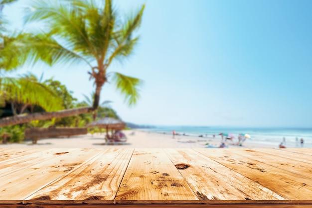 Parte superior de la mesa de madera con paisaje marino, palmera, mar en calma y cielo en playa tropical