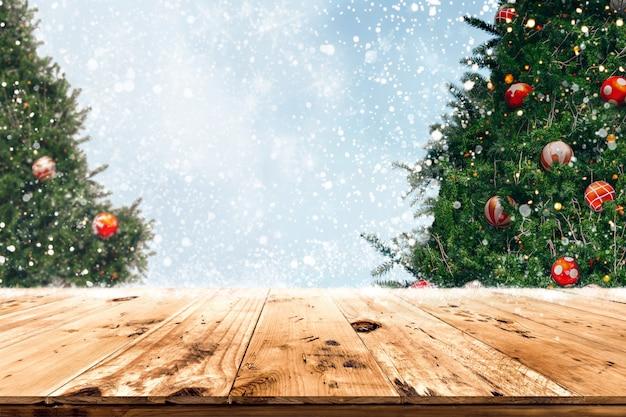 Parte superior de la mesa de madera vacía con hermoso árbol de navidad y nevadas de fondo