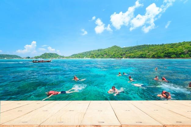 Parte superior vacía de la mesa o mostrador de madera y vista de la playa tropical en las islas phi phi