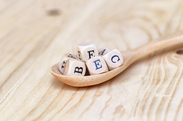La parte superior ve la palabra de vitaminas hecha de letras de madera en la mesa y abcde en la cuchara de madera