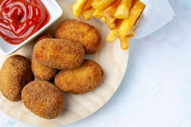 Parte superior de la vista de croquetas con patatas fritas y tomate frito.