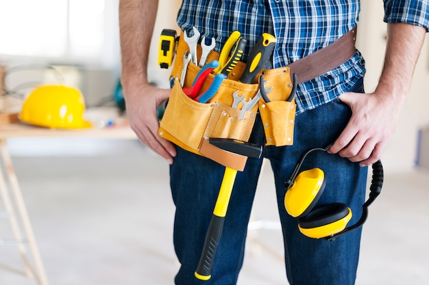Parte del trabajador de la construcción con cinturón de herramientas