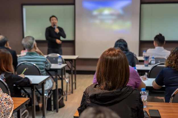 La parte trasera de la audiencia escucha al orador asiático con un traje informal en el escenario frente a
