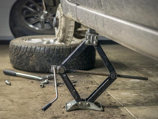 La parte trasera del automóvil en el garaje con la rueda quitada.