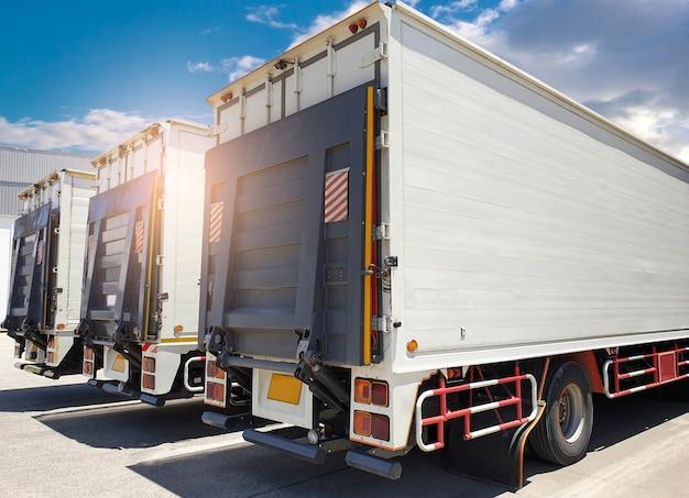 Parte trasera de un camión, camión elevador hidráulico de puerta en estacionamiento en el almacén. transporte de carga y logística.
