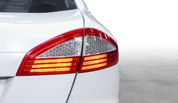 La parte trasera de un coche crossover caro blanco: parachoques, tapa del maletero, luz trasera en la parte trasera fondo blanco