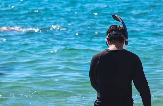 Parte trasera de un hombre vistiendo snorkel para bucear bajo el agua del mar.