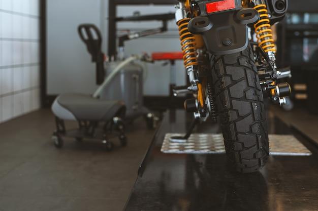 La parte trasera de las motos clásicas de pie en el taller de reparaciones.