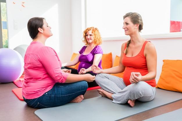 Partera que entrena a las mujeres embarazadas durante los ejercicios de relajación i