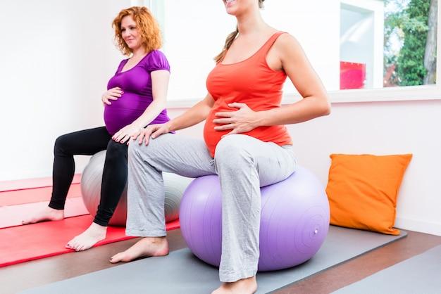 Partera que entrena a las mujeres embarazadas durante los ejercicios de relajación