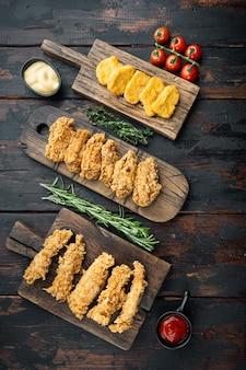 Partes de pollo frito crujiente en la vieja mesa de madera oscura, vista superior.