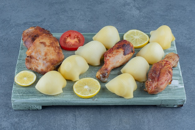 Partes de pollo a la parrilla y patatas hervidas sobre tabla de madera.