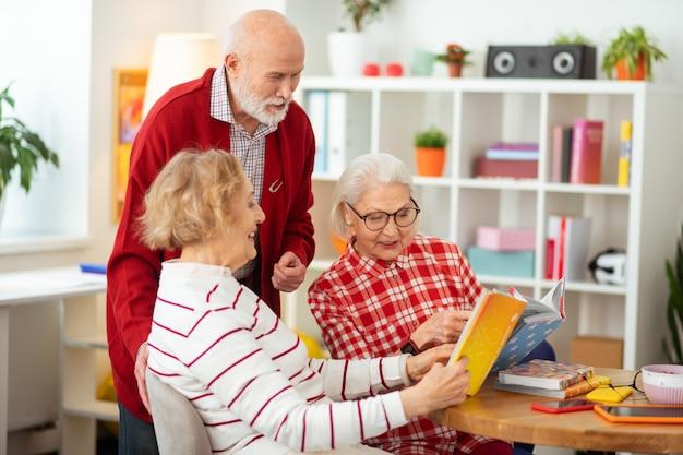 Participar en la discusión. bonitas mujeres felices sentadas juntas mientras hablan de diferentes libros