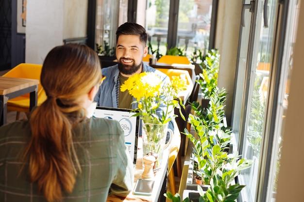 Participar en la discusión. hombre barbudo alegre sonriendo mientras disfruta de la conversación con su colega