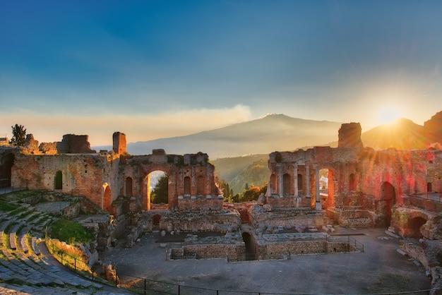 Particular del antiguo teatro de taormina con el volcán etna en erupción al atardecer