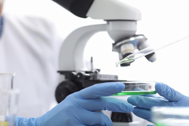 Partículas de examen microscópico, manos enguantadas