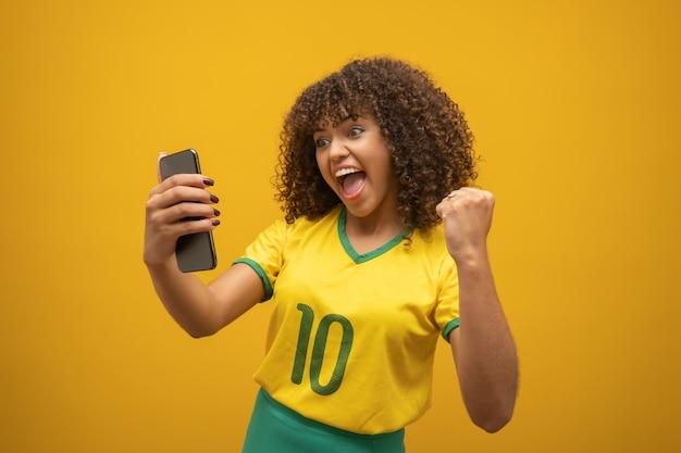 Partidario del equipo de fútbol brasileño celebrando un gol mirando el teléfono inteligente