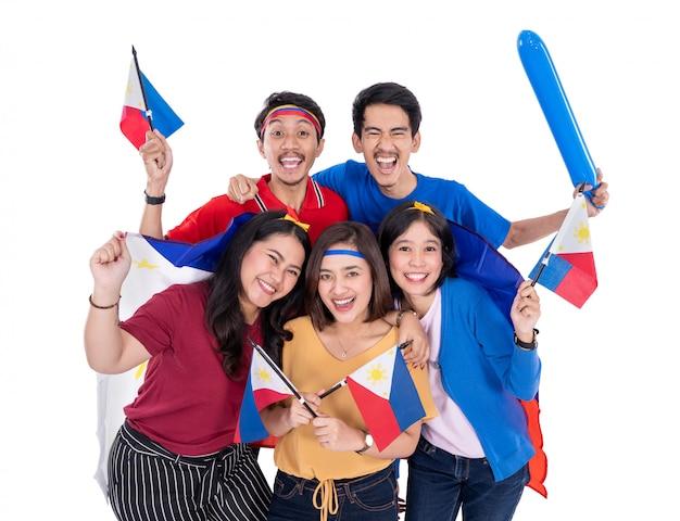 Partidario joven asiático emocionado que sostiene la bandera de filipinas