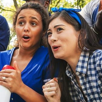 Partidarios del béisbol femenino viendo a su equipo perder el juego