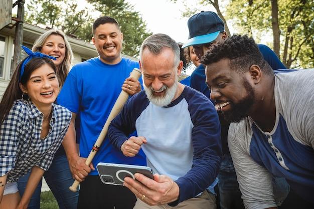 Partidarios de béisbol viendo a su equipo ganar el juego en un teléfono móvil
