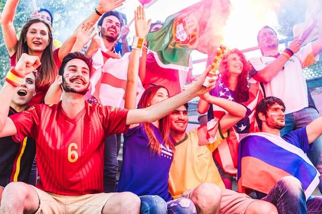 Partidarios felices fanáticos en el estadio con banderas y bomba de humo
