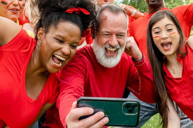 Partidarios que ven a su equipo ganar el juego en un teléfono móvil