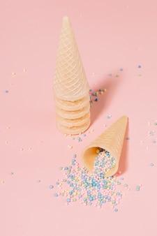 El partido asperja las bolas que se derraman del cono de la galleta contra fondo rosado
