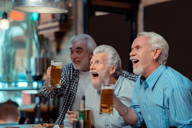 Partido de fútbol importante. los fanáticos del fútbol se sienten emocionados mientras ven un partido importante