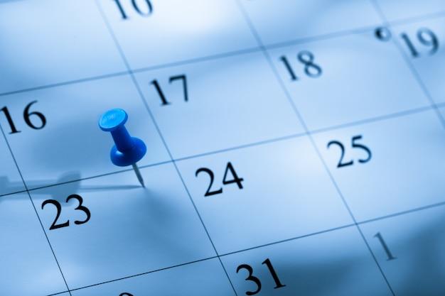 Pasador bordado en un calendario el 23 con enfoque selectivo