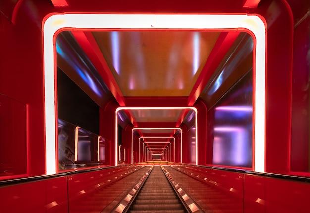 Pasaje circular de escaleras mecánicas con luz roja