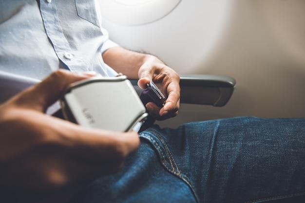 Pasajero abrocharse el cinturón de seguridad mientras está sentado en el avión para un vuelo seguro