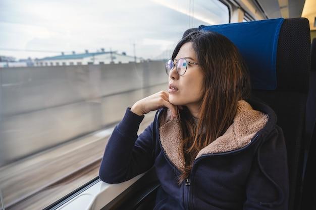 Pasajero asiático de la señora joven que se sienta en un humor deprimido al lado de la ventana dentro del tren que viaja