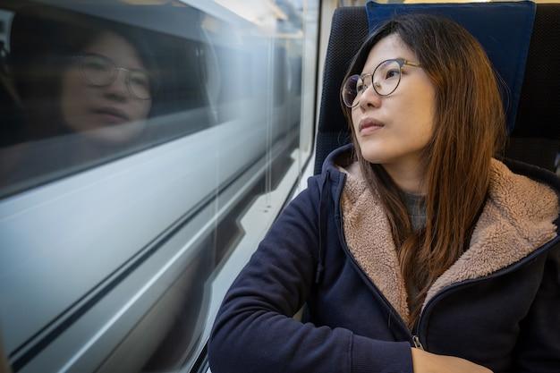 Pasajero asiático de la señora joven que se sienta en un humor deprimido al lado de la ventana dentro del tren