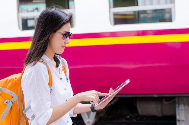 Pasajero de mujer asiática usando la tableta de tecnología en el tren