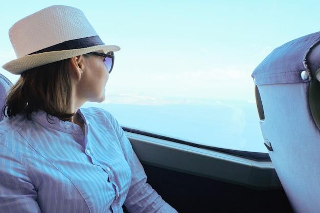 Pasajero mujer con sombrero sentado en el autobús mirando por la ventana, transporte turístico, cielo y mar en la ventana, espacio de copia
