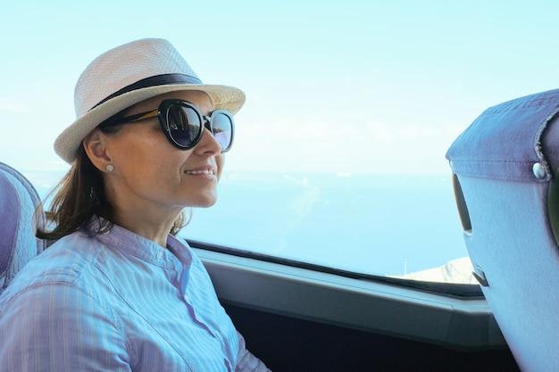 Pasajero mujer con sombrero sentado en el autobús mirando por la ventana