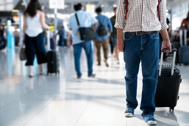 El pasajero con tarjeta de embarque en la mochila y maleta con ruedas en la estación de transporte.