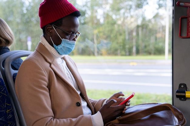 Pasajero con teléfono móvil lleva mascarilla sentado en autobús público
