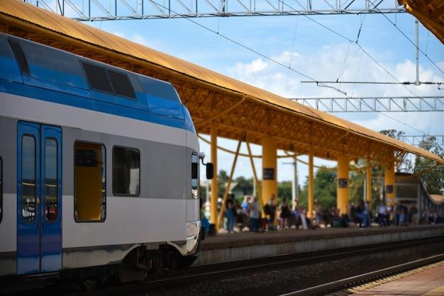 Los pasajeros esperan un tren rápido en una estación de ferrocarril de la ciudad.