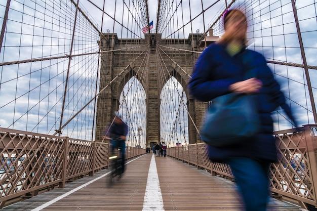 Pasajeros y turistas indefinidos caminando y montando una bicicleta en el puente de brooklyn.