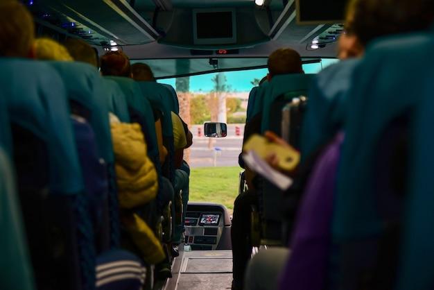 Los pasajeros viajan en un autobús turístico en los asientos.