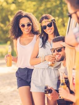 Pasando el tiempo con amigos. dos mujeres jóvenes sonrientes de pie cerca de la minivan mientras tres personas sentadas en su interior