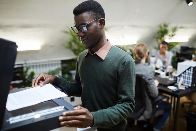 Pasante africano con escáner en la oficina